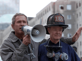 U.S. President George W. Bush, standing next to retired firefighter Bob Beckwith, speaks to volunteers and firemen as he surveys the damage at the site of the World Trade Center in New York on September 14, 2001.