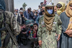 Taliban members stand next to people rushing to pass to Pakistan from the Afghanistan border in Spin Boldak on Sept. 25, 2021.