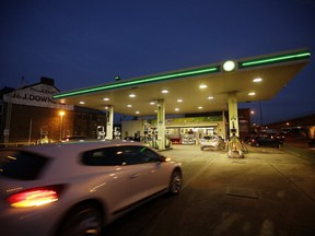 An automobile drives onto the forecourt of a gas station operated by BP Plc at night in London, U.K., on Tuesday, Jan. 14, 2014.