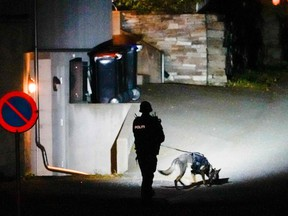 A police officer uses a sniffer dog at the scene they were investigating in Kongsberg.