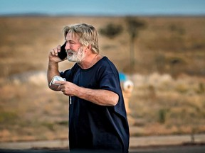 """Alec Baldwin speaks on the phone in the parking lot outside the Santa Fe County Sheriff's Office in Santa Fe, N.M., after he was questioned about a shooting on the set of the film """"Rust"""" on the outskirts of Santa Fe, Thursday, Oct. 21, 2021."""