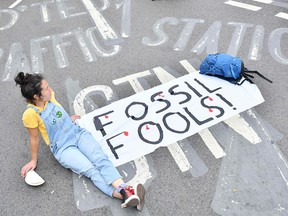 A climate activist from the Extinction Rebellion group blocks London Bridge during a protest on Aug. 31, 2021. The group is promising to bring traffic to a standstill in Glasgow during the COP26 climate conference to be held Oct. 31 to Nov. 12.