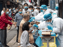 Medical workers take swab samples from residents to be tested for the COVID-19 coronavirus, in a street in Wuhan on May 15, 2020.
