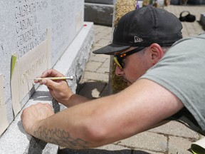 """JohnStewart LeBaron prepares the stencilled name of his cousin, David Alwyn """"Al"""" Forneri, for sandblasting into a monument Monday, July 15, 2019 in Belleville. Belleville council is to consider a request by a city resident to add a name to the Second World War monument."""
