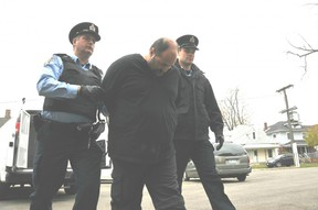 In this file photo from 2012, Chatham-Kent police special constables John Carter, left,  and Tyler Bergsma, right, escort Ronald Inghelbrecht of Chatham to the local jail after being sentenced to five years for sexual assault and two years for possession of child pornography. He is now facing new sex-related charges that are before the court. (Daily News file photo)