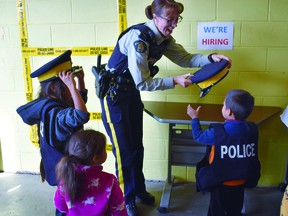 Sgt. Jolene Nason lets some local kids try on police hats during an open house at the Devon RCMP detachment in 2019. (Emily Jansen)