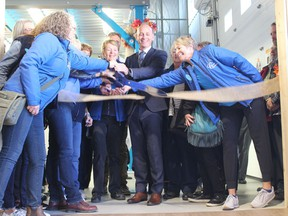 Mayor Jeff Genung helps members of the Cochrane Activettes officially open up the new large expansion of the Activettes's food bank. Patrick Gibson/Cochrane Times