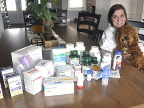 Melissa Snowden, and dog Trouper, of Egmondville, ON, displays all the medications she needs to ingest daily as she lives with Cystic Fibrosis. The 36-year-old is holding out hope that a new drug, Trikafta, will be available in Canada and allow her to stop taking so many other medications and dietary supplements. ANDY BADER