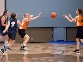 Mayerthorpe Tigers' Autumn Chittick passes back to teammate Alex Jeppesen during a tournament game against a Whitecourt team. The teams faced off Friday morning in the NCJHAA Junior Basketball Championship. Four teams, also including Edson and Evansburg, competed in the competition.  Brigette Moore | Mayerthorpe Freelancer