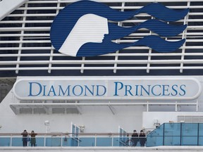 Masked passengers look on from onboard the coronavirus-hit Diamond Princess cruise ship docked at Yokohama Port, south of Tokyo, Japan, on Feb. 20.