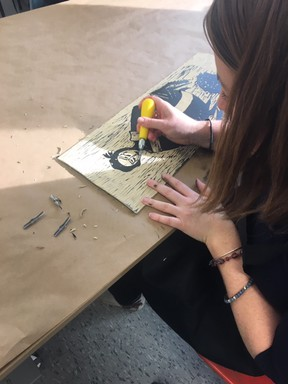 A student from Ms. Johnston's Grade 12 class at St. Mary's Catholic High School cuts a design into lino to create a printing plate. The class worked with London artist Jessica Woodward on a collaborative surrealism printmaking project. (Woodstock Art Gallery)