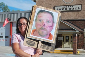Cheryl Hillier, wife of Casey Hillier, held a sign at Thursday's protest with a photo of her husband that shows him with cuts and bruising on his face and forehead. KEITH DEMPSEY