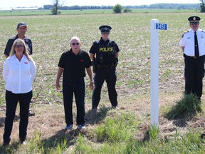 Farmer and South Dundas Coun. Archie Mellan (back) hosted a small gathering Wednesday morning for the first civic  address sign in the community as part of the Emily 911 Farm Entrance Program. From left are Jackie Kelly-Pemberton (regional director, Ontario Federation of Agriculture), Jim Shaw (director for Dundas Federation of Agriculture), OPP Const. Laura Dargie (Winchester detachment) and Cameron Morehouse (chief of South Dundas Fire & Emergency Services). Photo on Wednesday, June 17, 2020, in Hulbert, Ont. Todd Hambleton/Cornwall Standard-Freeholder/Postmedia Network
