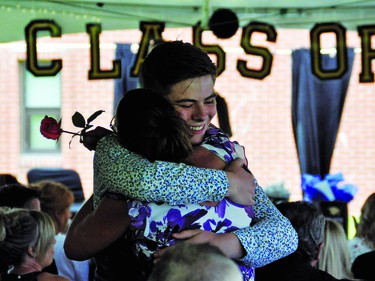 J.T. Foster graduate Dallon Southgate gives mom Brenda a hug after presenting her with a rose during a graduation ceremony Saturday afternoon. The school held three separate graduation ceremonies under a tent on the lawn north of the school to keep each of the outside gatherings under total 100 people, the current maximum the Alberta government is allowing.