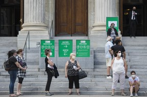 People wear face masks as they wait to enter the Museum of Fine Arts in Montreal, Saturday, June 6, 2020, as the COVID-19 pandemic continues in Canada and around the world. A new poll suggests Canadians are increasingly wearing protective face masks as they emerge from months of isolating at home to curb the spread of COVID-19.THE CANADIAN PRESS/Graham Hughes
