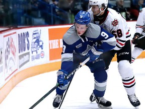 Landon McCallum of the Sudbury Wolves battles for the puck with Adrien Beraldo of the Niagara Ice Dogs during Sunday Night OHL action from the Sudbury Community Arena.