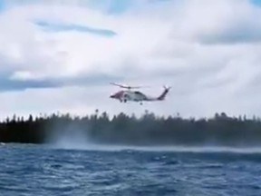 A coast guard helicopter assists in the rescue of two kayakers who capsized in Lake Huron near Providence Bay.
