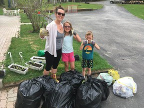 Amy, Eve and Russel Southward stand beside the mound of garbage that they collected as part of the clean up challenge at Cochrane Public School..TP.jpg