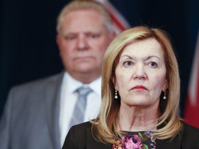 Christine Elliott, deputy premier and minisiter of health, with Premier Doug Ford in background.