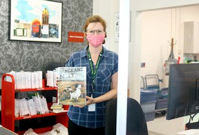 Katie McNamara, library assistant at the Delhi branch of the Norfolk County Public Library, stands behind a sneeze guard at the front desk while wearing a mask as part of the COVID-19 emergency response. Ashley Taylor photo