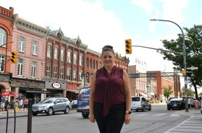"""Ryzhome Networks and Festival Hydro vice president of IT Delia Campbell stands at the corner of Ontario Street and Downie Street, one of Stratford's 24 """"smart intersections"""" at which traffic lights now have the ability to communicate with autonomous vehicles. (Galen Simmons/The Beacon Herald)"""
