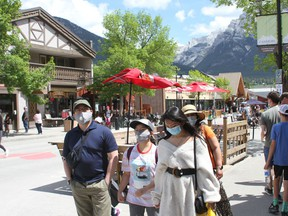 Tourists walk in downtown Main Street in Canmore in the open pedestrian area. Photo Marie Conboy.