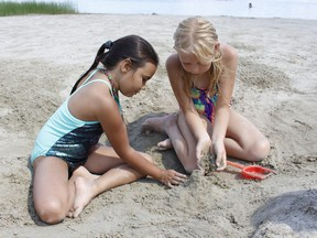 Jazielle Rochon, 8, on left, along with her friend, Taya Myer, 9, were building sand castles and playing at Gillies Lake Beach on a sunny and humid Wednesday afternoon. The heat is expected to continue with Timmins' daytime temperatures for Thursday and Friday predicted to reach highs of 30 C though the Environment Canada's forecast for the area also calls for cloudy conditions and chance of showers both days.  RICHA BHOSALE/The Daily Press