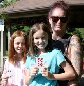 Keri Cooper poses with her daughters Lena, 10, left, and Olivia, 8, in Watford's Sunken Gardens. The Watford woman is behind a town-wide scavenger hunt currently underway. (Tyler Kula/The Observer)