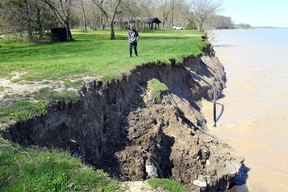 """Keagan Chambers walks along the eroded shoreline at Wheatley Provincial Park on May 14, 2019. IThe Ontario government on Aug. 14 launched its first-ever climate change impact assessment to better understand where and how climate change will affect """"communities, critical infrastructure, economies and the natural environment."""" File photo/Postmedia Network"""