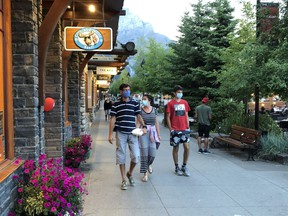 Visitors to Banff follow the mandatory mask bylaw on the main street pedestrian strip in August. Photo Marie Conboy.