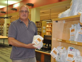 The Cornwall Public Library's communications and programs manager Pierre Dufour holding on of the many grab-bags being offered, on Tuesday August 4, 2020 in Cornwall, Ont. Francis Racine/Cornwall Standard-Freeholder/Postmedia Network
