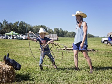 Jill Byers who owns Blue Ridge Farms with her husband gave little cowboy Easton Moore a demo on how to rope a cow bale. Byers opened her farm up to visitors to tour it as part of Alberta's Open Farm Days.  Brigette Moore