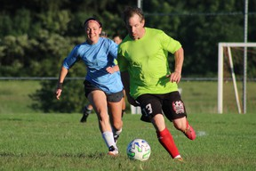 Jason Lingard defends the ball against Sadie Boyd on Friday night during an adult recreational soccer league at the Norfolk County Youth Soccer Park. Blue team won the game 4-0. (ASHLEY TAYLOR)