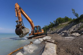 Cody Rahn of Huron District Contracting moves a boulder that will form part of a barrier against record-high water levels on the shoreline of Lake Huron just north of Bayfield on Sept. 1. Mike Hensen/Postmedia Network