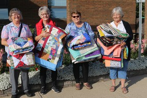 Arts N Craft Guild members Clara, Vi, Peggy, and Anne donating handmade quilts to the John A Smith Manor.