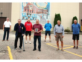 Past and present members of teams coached by Roy Dagenais recently gathered to present him with a plaque to commemorate his 26 years as a coach in the Pembroke Sportsmen's Hockey League. On hand for the presentation outside the Pembroke Memorial Centre (from left) were Daniel Levasseur, Graham Matthieu, league president Jerry Johnston, Dagenais, Joel Levasseur, Ed Cotnam and Denis Levasseur.