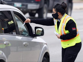 A woman conducts screening for the COVID-19 drive-through testing site in Winnipeg on Wed., Sept. 23, 2020. By mid-morning, there were 200 vehicles backed up with the expected wait time stretching into the lunch hour, the woman said. Kevin King/Winnipeg Sun/Postmedia Network