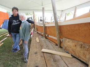 Chuck Commanda, Algonquin knowledge keeper, and Mary Farrar, from Friends of Kingston Inner Harbour, stand next a birch bark canoe on Saturday. The canoe is being hand built in the coming weeks in Douglas R. Fluhrer Park. (Meghan Balogh/The Whig-Standard)