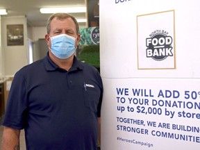 Lakeview Rona manager Al McCauley stands beside a banner promoting the Lowe's Canada 2020 Heroes campaign. The store, as well as Rona Lakeview Builders Supplies, is collecting donations all September for the North Bay Food Bank. Michael Lee/The Nugget