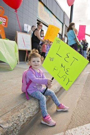 Two-year-old Brooklynn Doucette joined the rally Thursday afternoon to show their support for Bugz and Beanerz Indoor Play Place and Creperie. The indoor playground is lobbying the government to be allowed to open to the public, after similar type businesses such as trampoline parks have opened their doors to the public. Brigette Moore