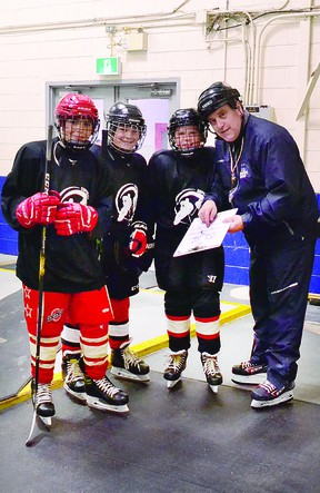 COACH FRANK AND THE BOYS: Players Anthony Spironello, Madden Glavota and Ryan Johnson (left to right) of a Sault Major Hockey Association under 13 cohort group receive instruction from coach Frank Porco prior to a recent on ice skills session. ALLANA PLAUNT/SAULT THIS WEEK
