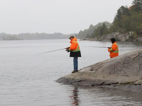 Leigh Channing and Bryan Loree fish in the rain near the boat launch on Ramsey Lake in Sudbury, Ont. on Tuesday September 15, 2020.