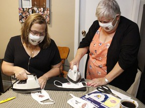 Joanne Hagger-Perritt, left, organizer of the local Kidney Walk event, along with her mom, Jacky Miller, were ironing some masks for bearing the name of her team in preparation for the virtual fundraising walk for the Kidney Foundation of Canada on Sunday, Sept. 27.   RICHA BHOSALE/The Daily Press