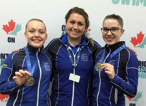 Sudbury Synchro Club coach Courtney Stasiuk stands between medal-winning swimmers Georgia Speck, left, and Stacie Kohan.