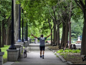 A man does arm exercises while walking his dog in Parc Lafontaine in Montreal on Wednesday, Sept. 2, 2020.