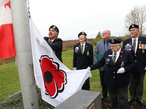 Chris Peters, left, of Branch 564, prepares to raise a poppy flag during a ceremony to launch the Poppy Campaign at Branch 76 of the Royal Canadian Legion in 2018.