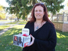 Erin Pollard, president of MADD Sarnia-Lambton, holds a Red Ribbon Project box that will be placed at local businesses through the holidays. Paul Morden/Postmedia Network
