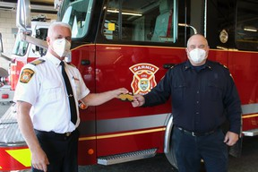 Chief Bryan VanGaver (left), with Sarnia Fire Rescue Services, hands Deputy Chief Ken Dwinnell his stripes on Nov. 2, on his first official day in the new post. Paul Morden/Postmedia Network