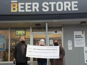 Wiarton and Sauble Beach Beer Store manager Trevor Couch, left, and Beer Store employee Shannon Gerencser, centre, present April Patry, executive director of the Bruce Peninsula Health Services Foundation, with a cheque for $7,682.20 in front of the Wiarton Beer store on Nov. 16 after a fundraising drive.
