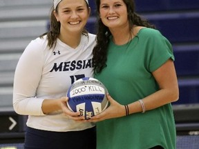 Paris native Holly Motheral presents a game ball to Mary Underman, a two-time All-American who reached 1,000 kills last season. Motheral is the head coach of the women's volleyball team at Messiah University in Pennsylvania.